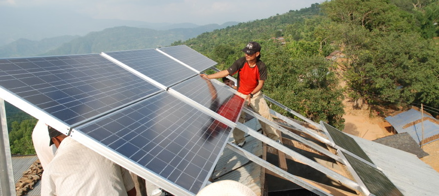 Enginners lift PhotoVoltaic panels into position on top of Shree Prabhat school in Dhawa, July 2010.